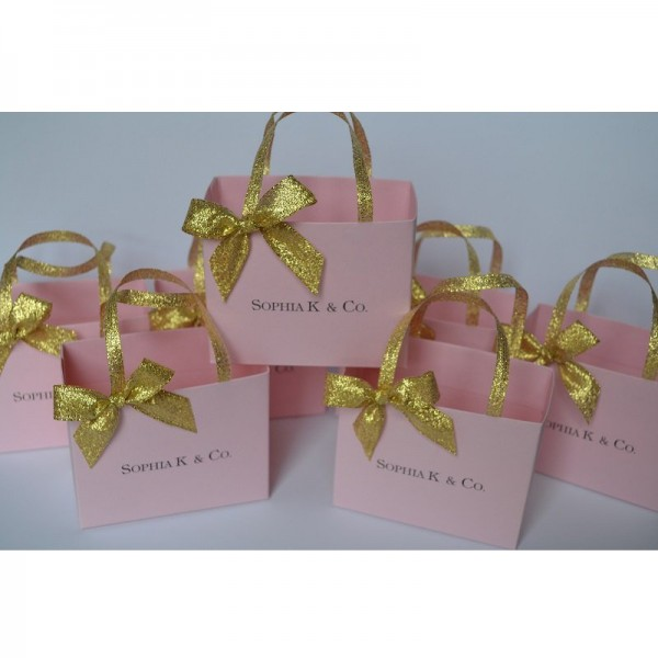 Pink party favor bags with gold ribbon